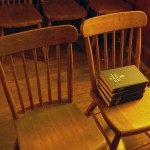 wooden chairs and hymnals in an old church building