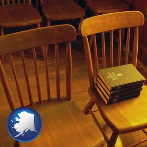 wooden chairs and hymnals in an old church building - with Alaska icon