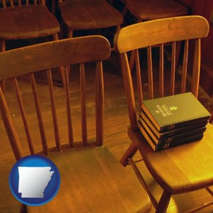 wooden chairs and hymnals in an old church building - with Arkansas icon