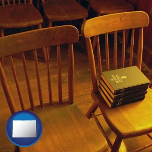 wooden chairs and hymnals in an old church building - with Colorado icon