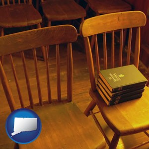 wooden chairs and hymnals in an old church building - with Connecticut icon