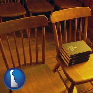 wooden chairs and hymnals in an old church building - with Delaware icon