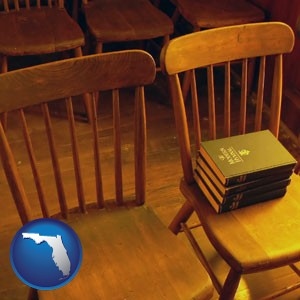 wooden chairs and hymnals in an old church building - with Florida icon