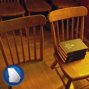 wooden chairs and hymnals in an old church building - with Georgia icon