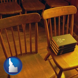 wooden chairs and hymnals in an old church building - with Idaho icon