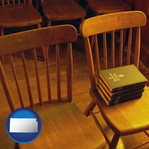wooden chairs and hymnals in an old church building - with Kansas icon