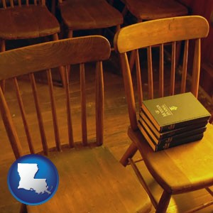 wooden chairs and hymnals in an old church building - with Louisiana icon