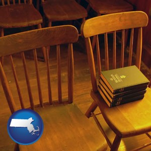 wooden chairs and hymnals in an old church building - with Massachusetts icon