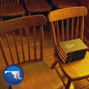 wooden chairs and hymnals in an old church building - with Maryland icon
