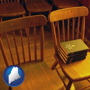 wooden chairs and hymnals in an old church building - with Maine icon