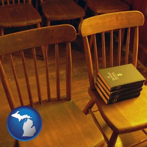 wooden chairs and hymnals in an old church building - with Michigan icon