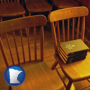 wooden chairs and hymnals in an old church building - with Minnesota icon