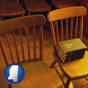 wooden chairs and hymnals in an old church building - with Mississippi icon