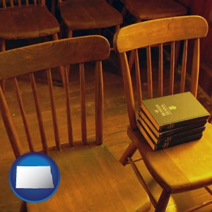 wooden chairs and hymnals in an old church building - with North Dakota icon