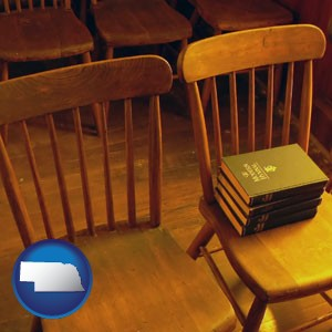 wooden chairs and hymnals in an old church building - with Nebraska icon