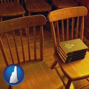 wooden chairs and hymnals in an old church building - with New Hampshire icon
