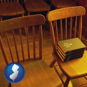 wooden chairs and hymnals in an old church building - with New Jersey icon
