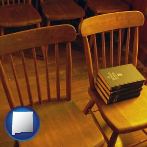 wooden chairs and hymnals in an old church building - with New Mexico icon