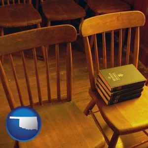 wooden chairs and hymnals in an old church building - with Oklahoma icon