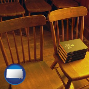 wooden chairs and hymnals in an old church building - with South Dakota icon