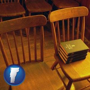 wooden chairs and hymnals in an old church building - with Vermont icon