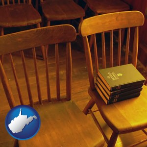 wooden chairs and hymnals in an old church building - with West Virginia icon