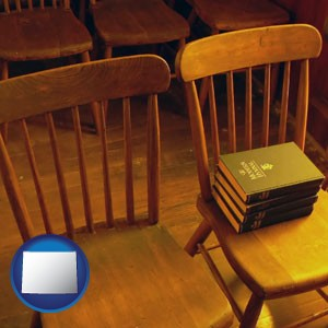 wooden chairs and hymnals in an old church building - with Wyoming icon